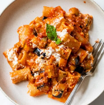 bowl with pasta, eggplant, ricotta, and fresh basil all covered in marinara sauce