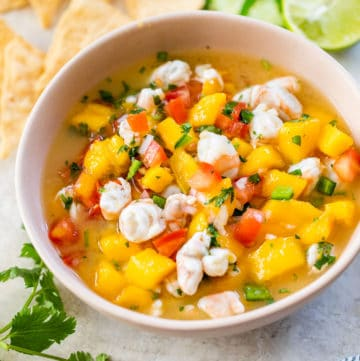 pink bowl with mango, shrimp and tomato beside a pile of tortilla chips