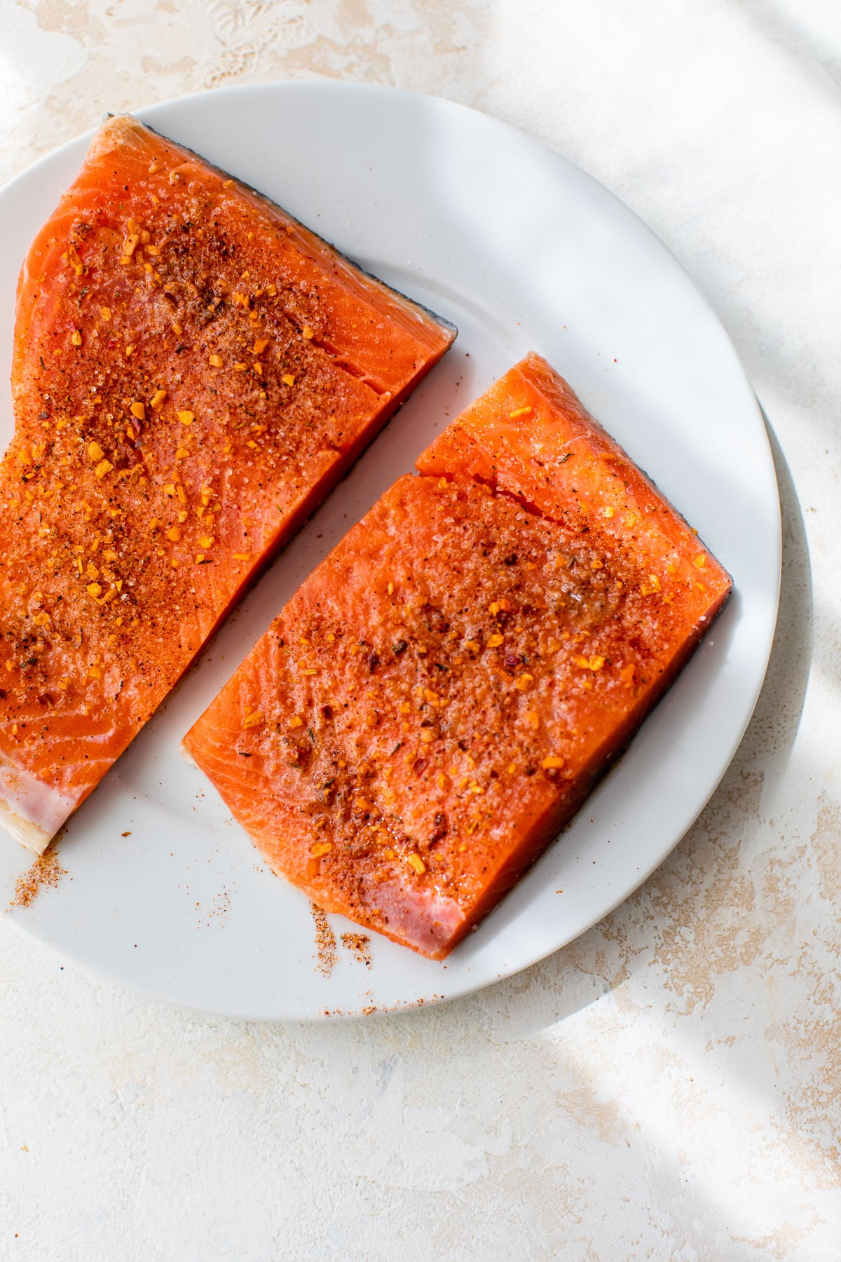 two raw salmon fillets on a white plate topped with seasoning