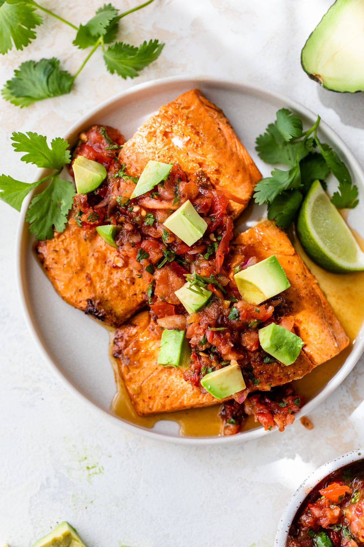 two salmon fillets on a plate topped with salsa and diced avocado