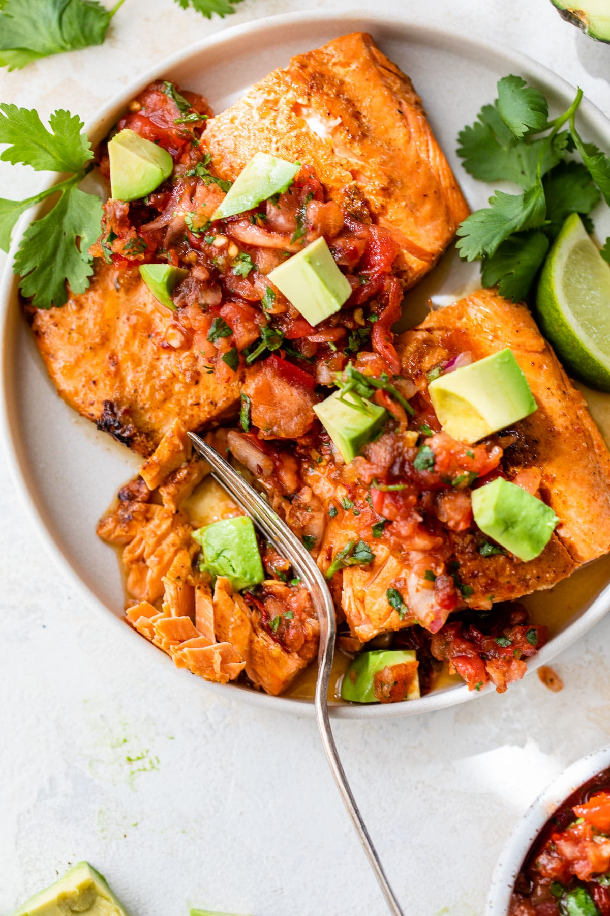two salmon fillets on a plate topped with salsa