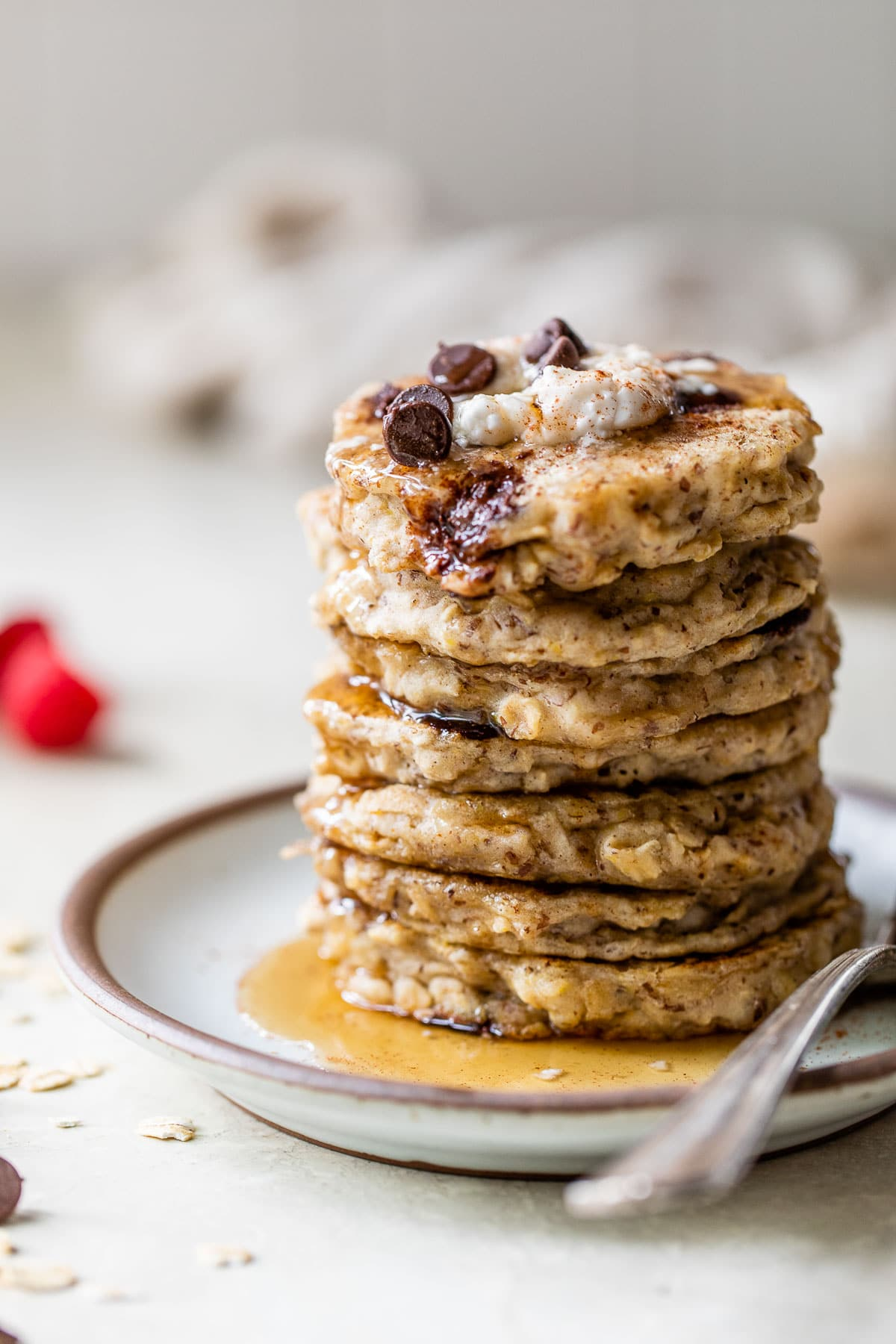 a stack of oatmeal pancakes on a plate with maple syrup