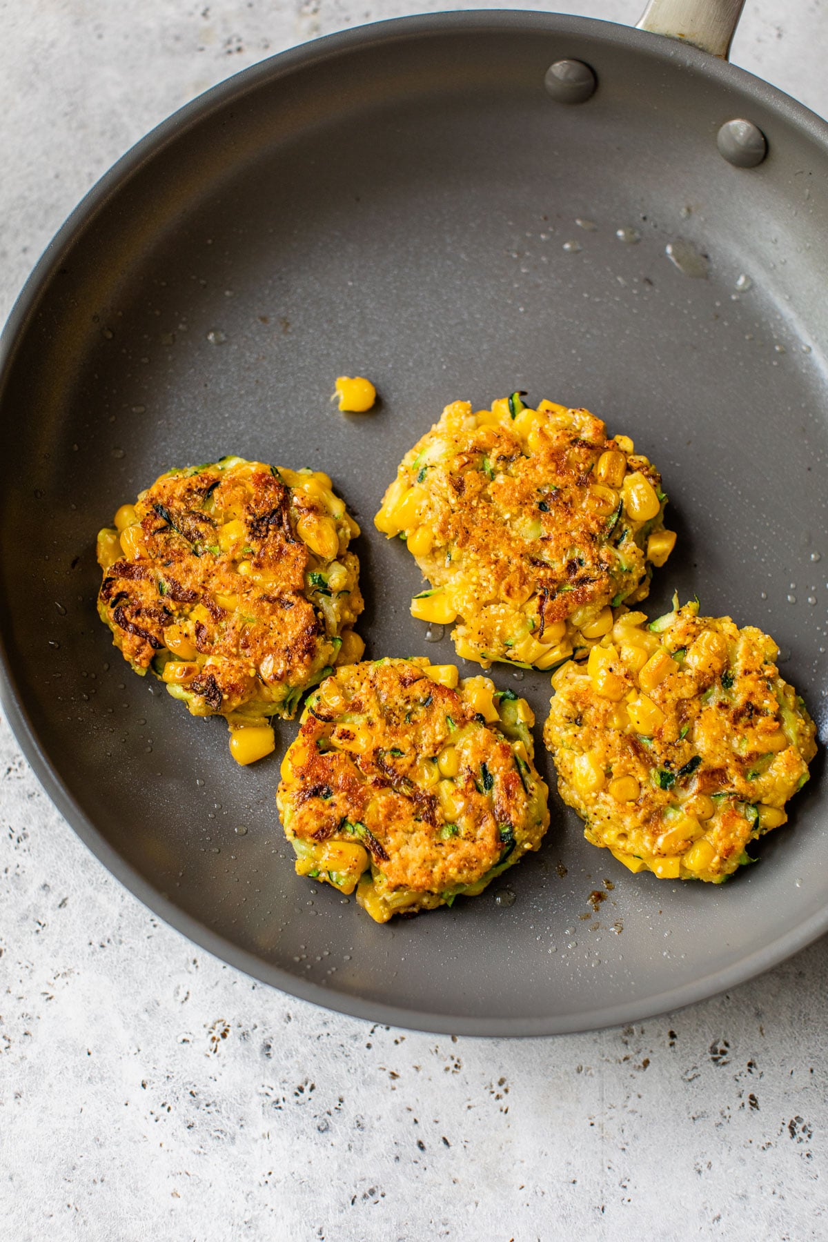 four corn fritters in a gray skillet