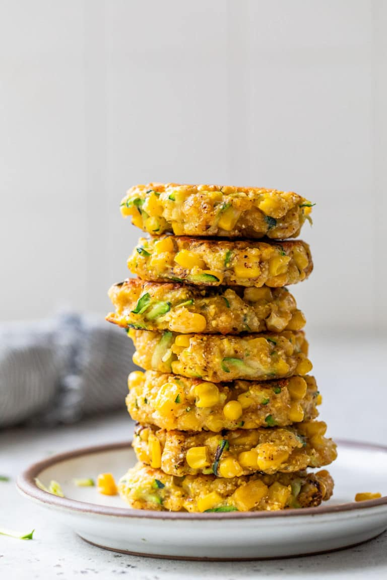 a large stack of fritters on a small white plate