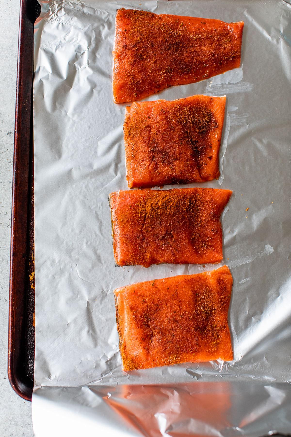 raw salmon fillets on a baking sheet sprinkled with cajun seasoning