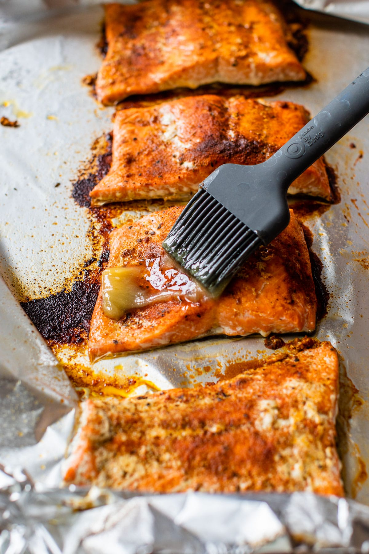 someone brushing butter overtop of baked salmon