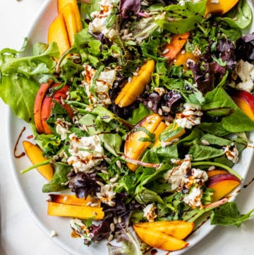 mixed greens on a platter with sliced peaches and burrata cheese