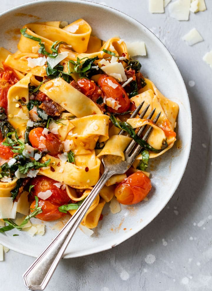long cooked pasta in a bowl with grape tomatoes and chopped basil