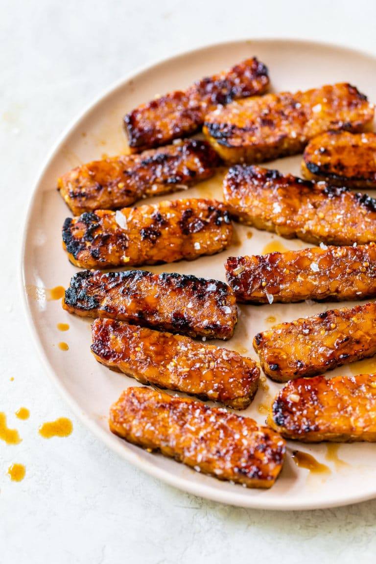 sliced tempeh with grill marks on a pink plate