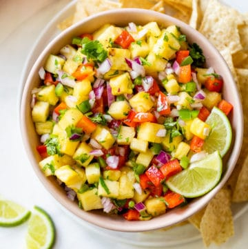 a small bowl of pineapple salsa beside a pile of tortilla chips