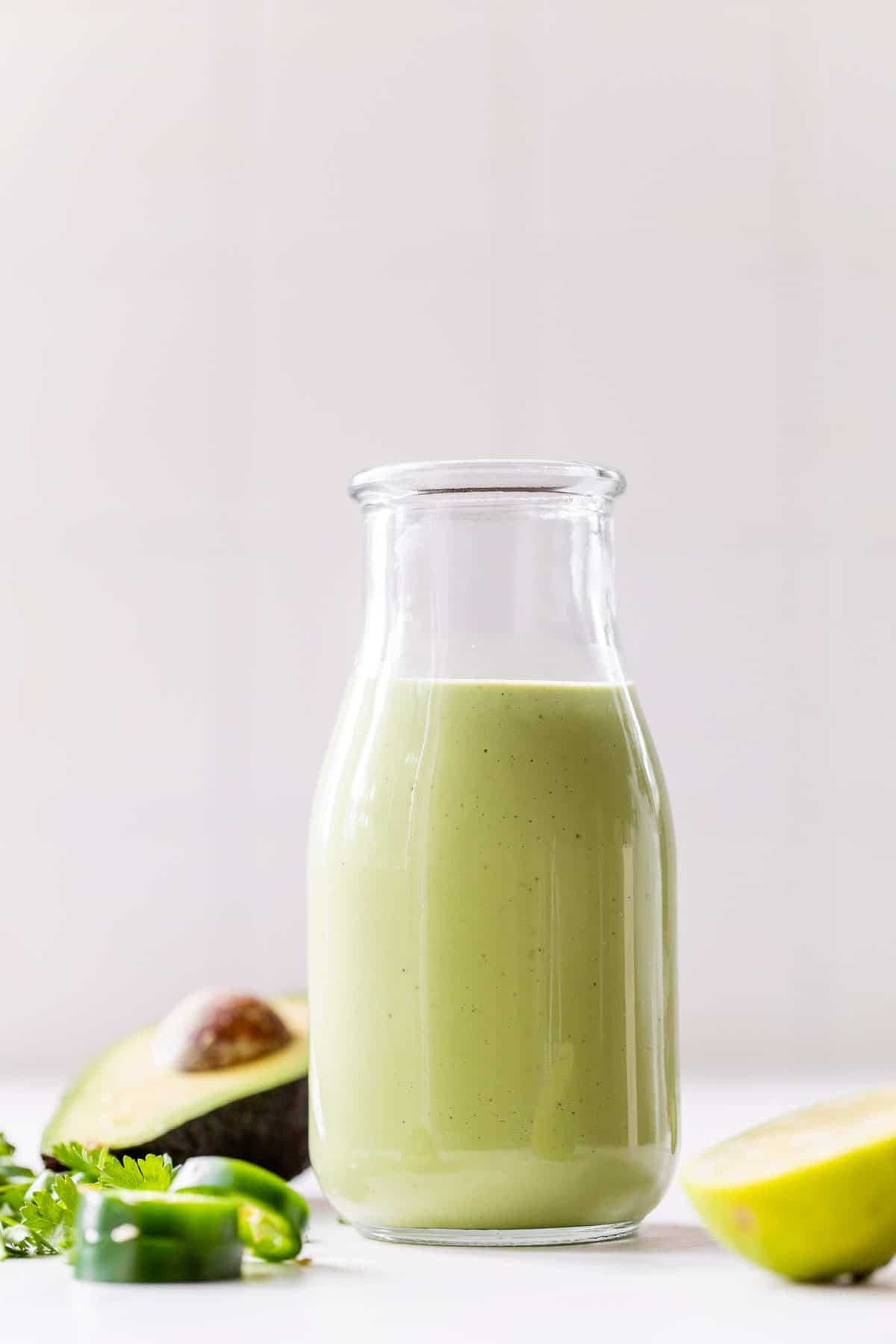 tall jar of green avocado dressing beside half an avocado