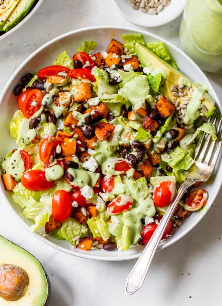 bowl filled with lettuce, sweet potatoes and black beans