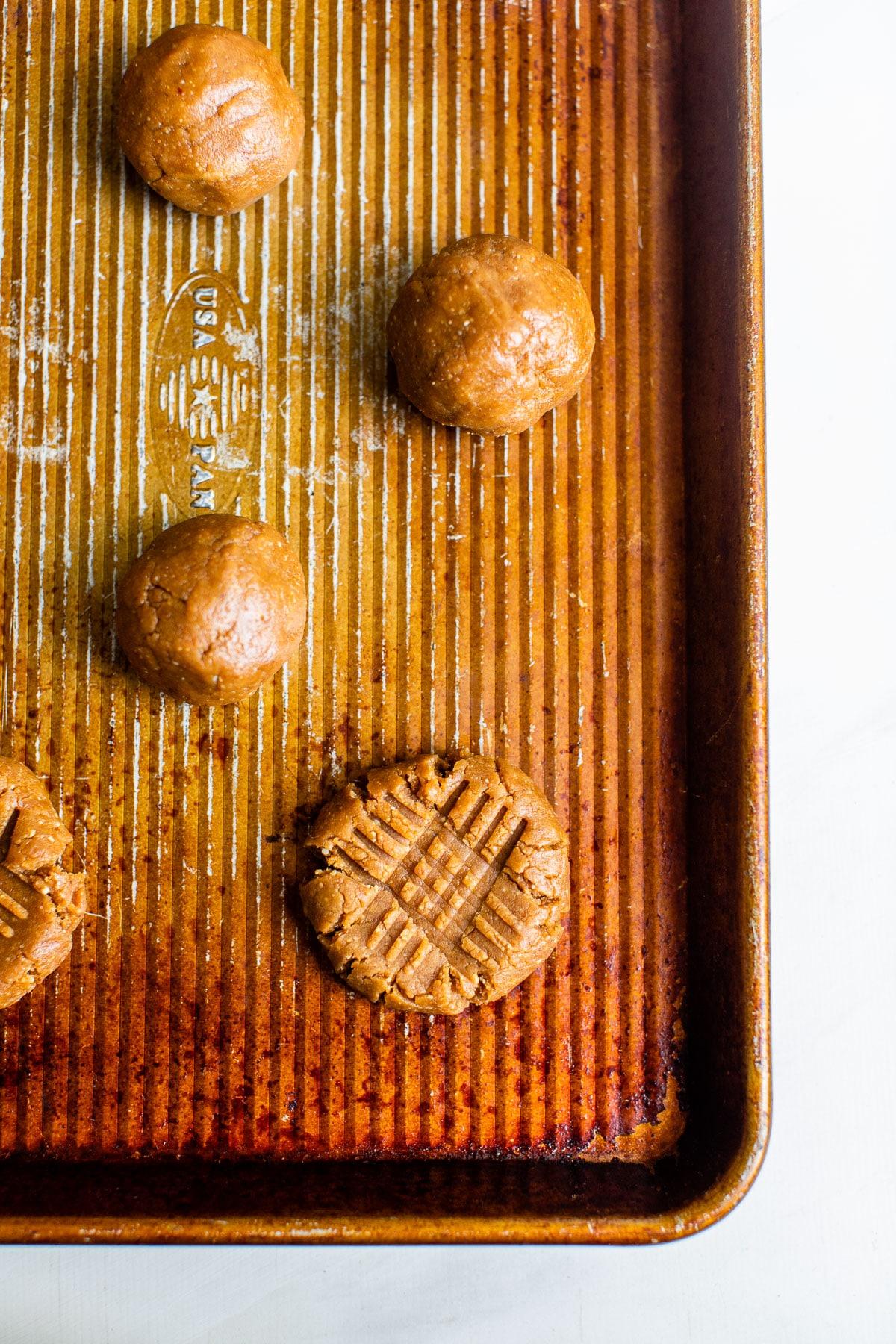 raw peanut butter cookie dough balls on a baking sheet