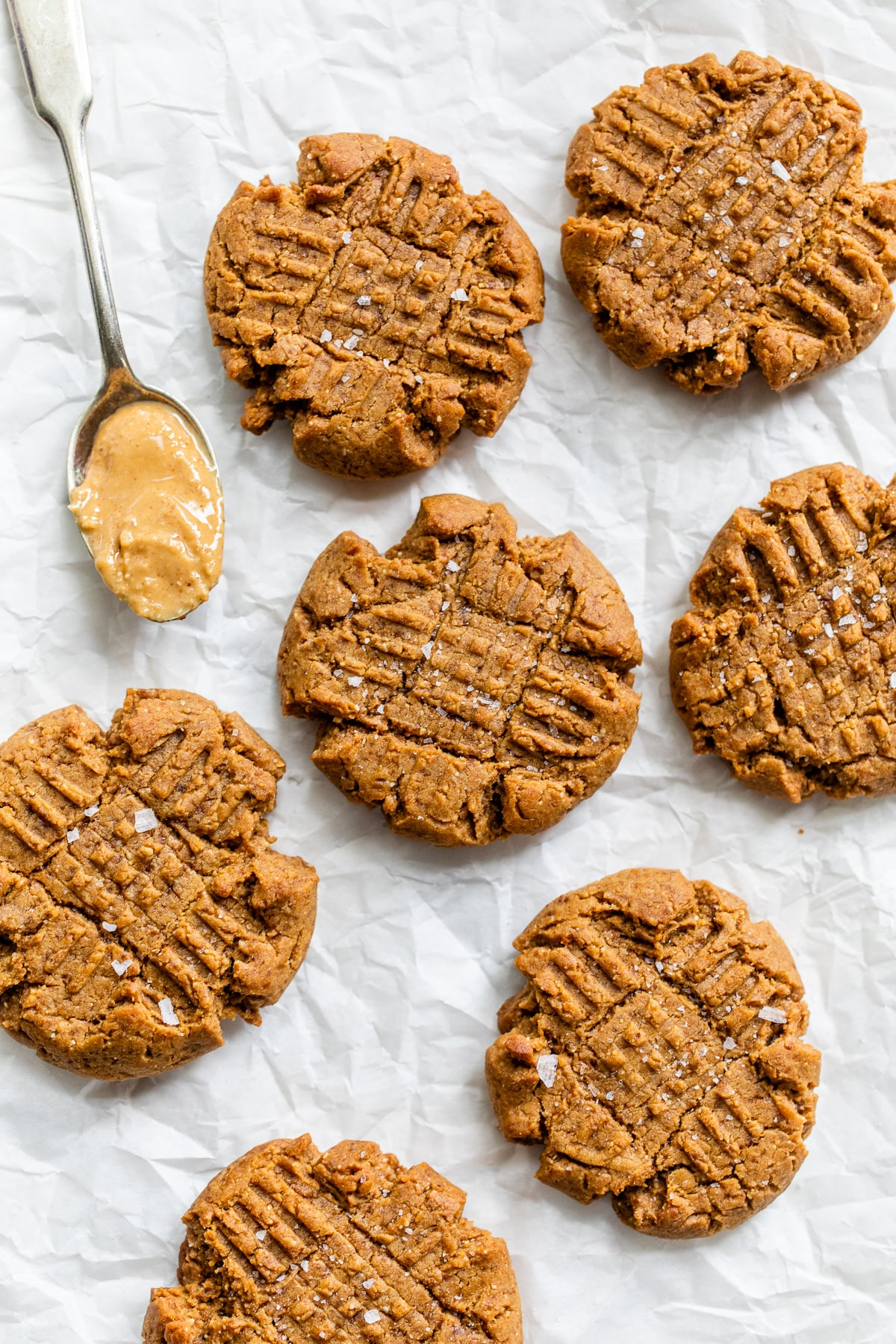 peanut butter cookies on parchment beside a spoon of peanut butter