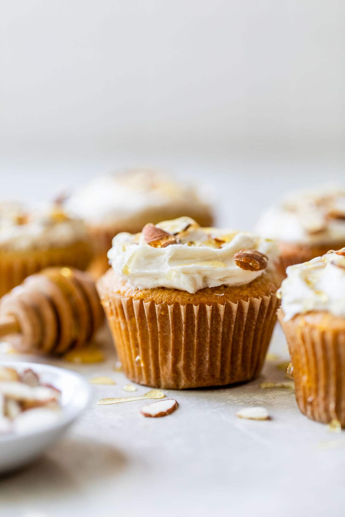 yellow cupcakes topped with white icing, sliced almonds and a drizzle of honey