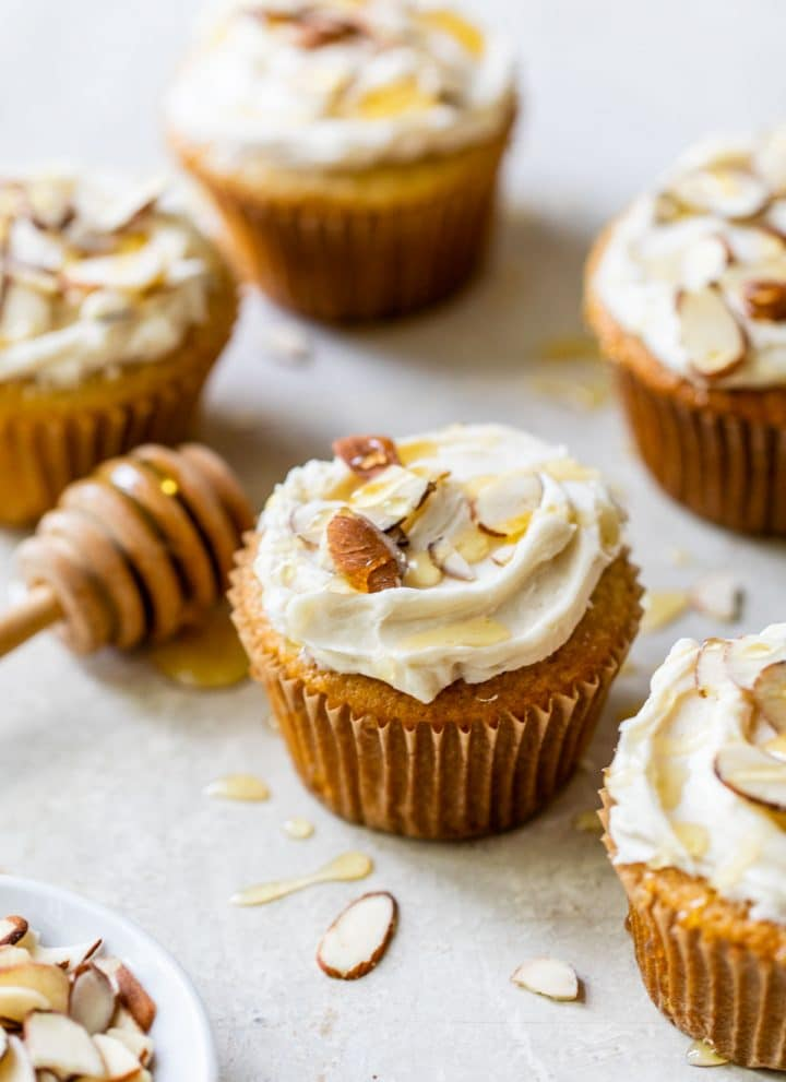 several almond cupcakes on a table topped with sliced almonds