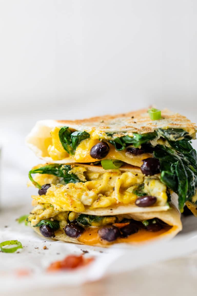 egg and black bean quesadilla stacked on parchment paper