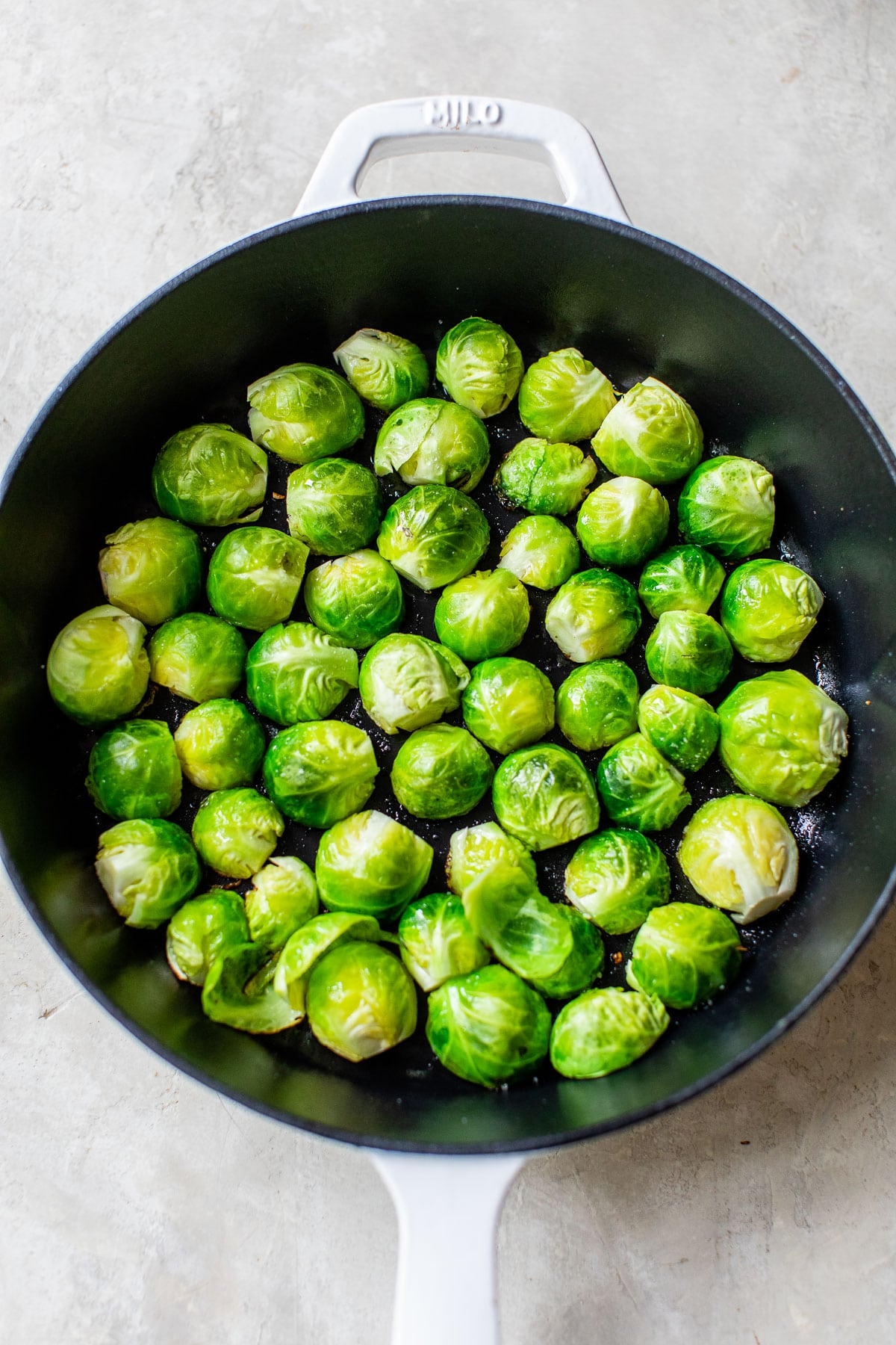 brussels sprouts cut side down in a cast iron skillet