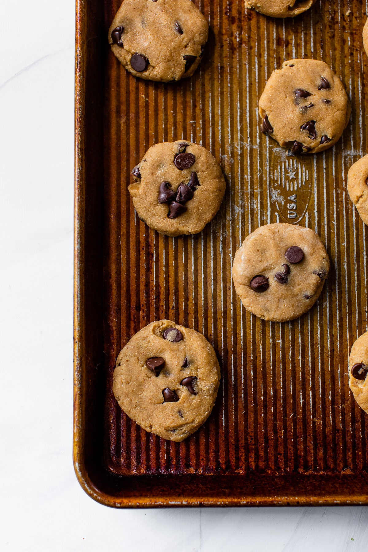 unbaked cookies with chocolate chips on a baking sheet