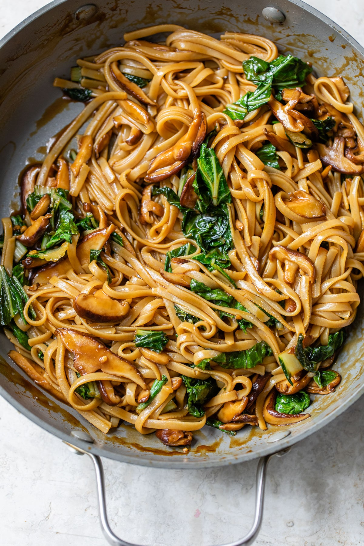 skillet with long noodles, mushrooms and bok choy