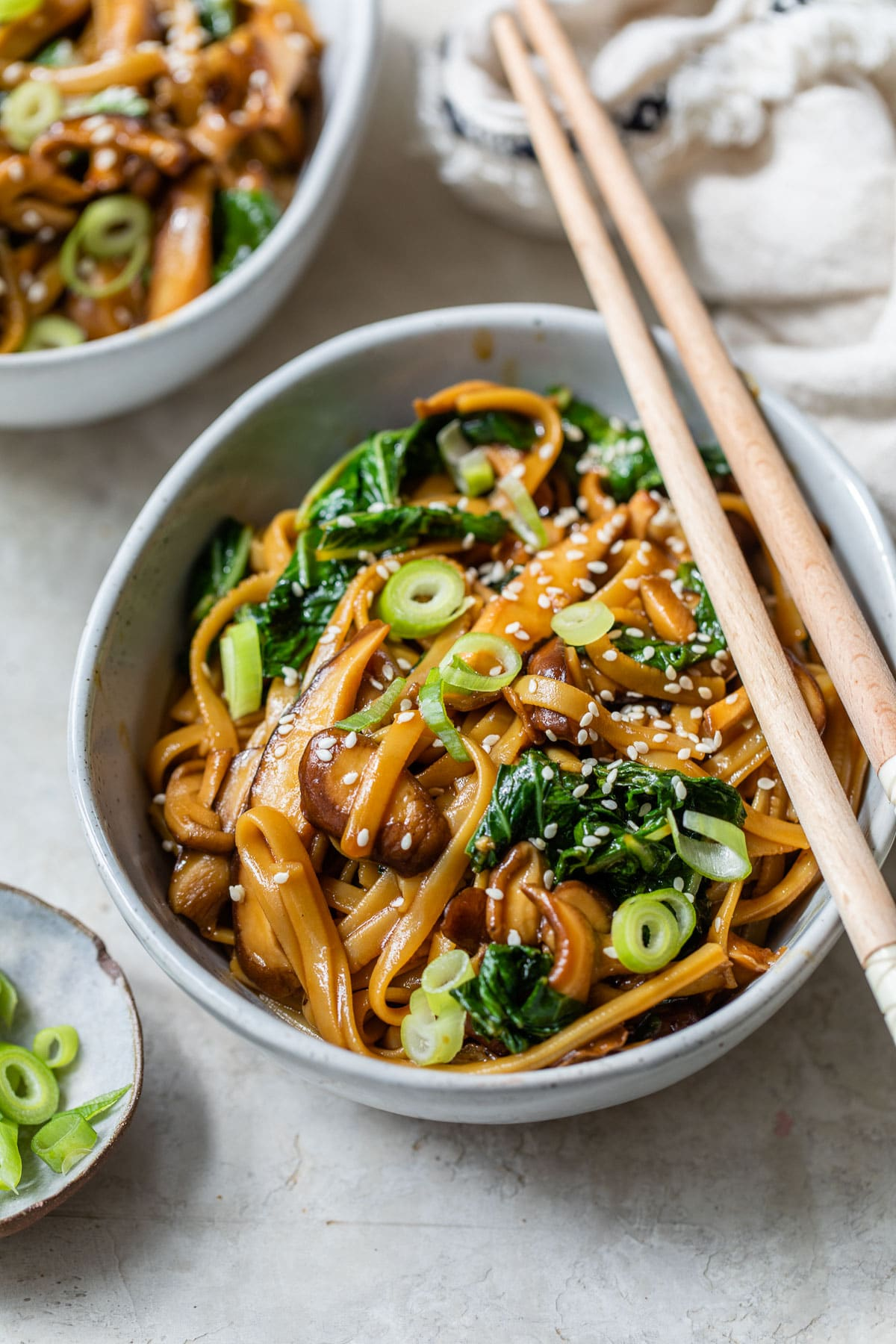 a bowl with long noodles, mushrooms and bok choy