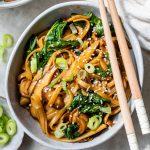 a bowl of long noodles with cooked bok choy and scallions