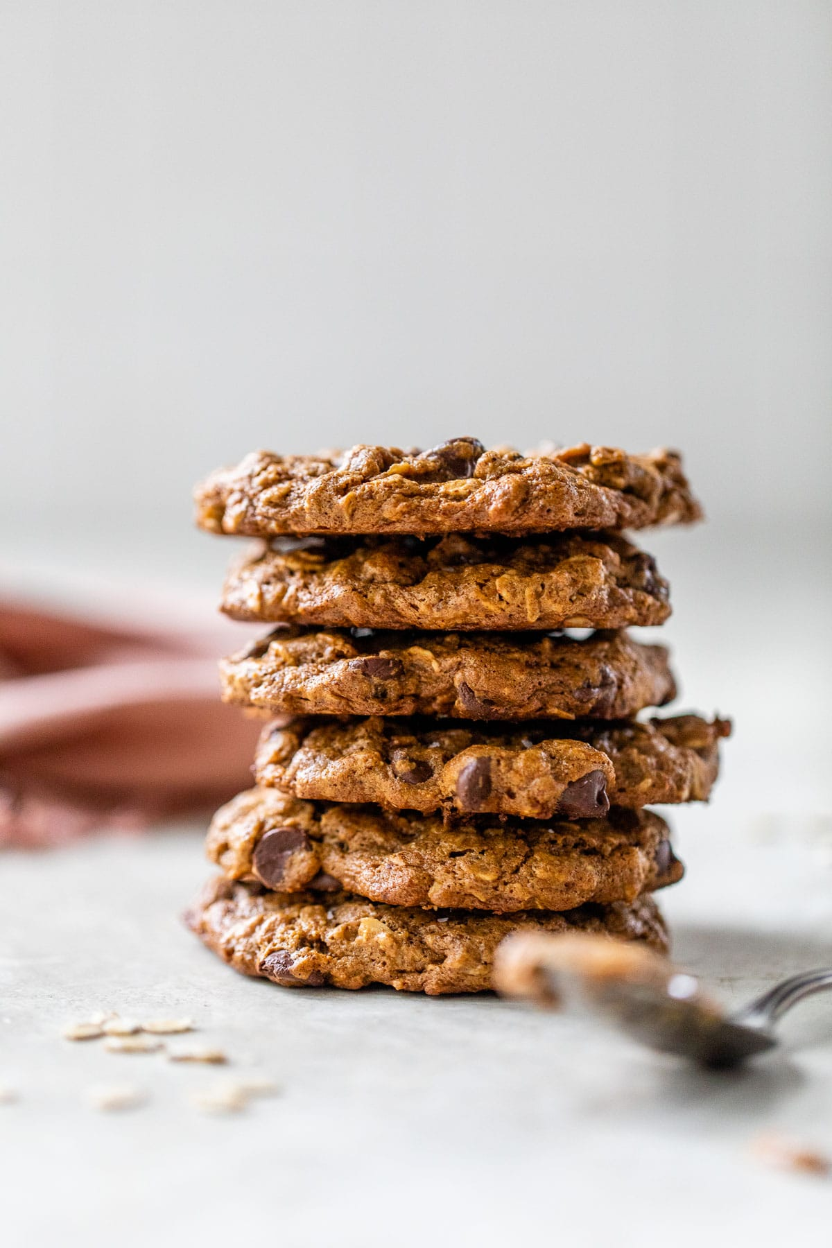 a stack of cookies beside a spoon of almond butter