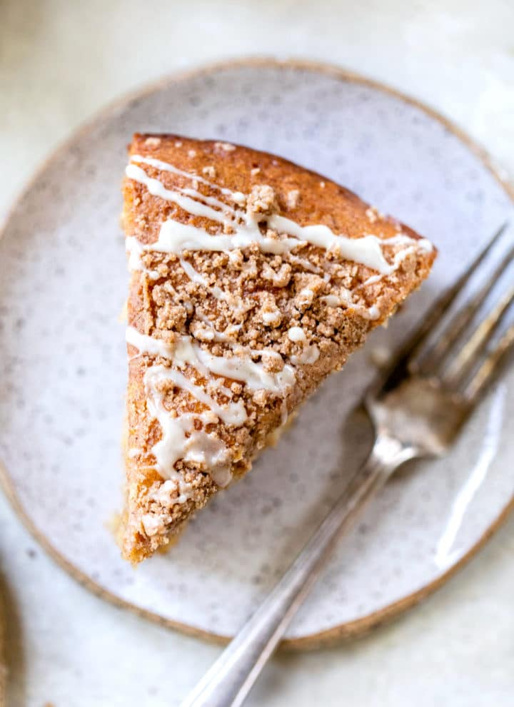a piece of coffee cake on a plate beside a fork