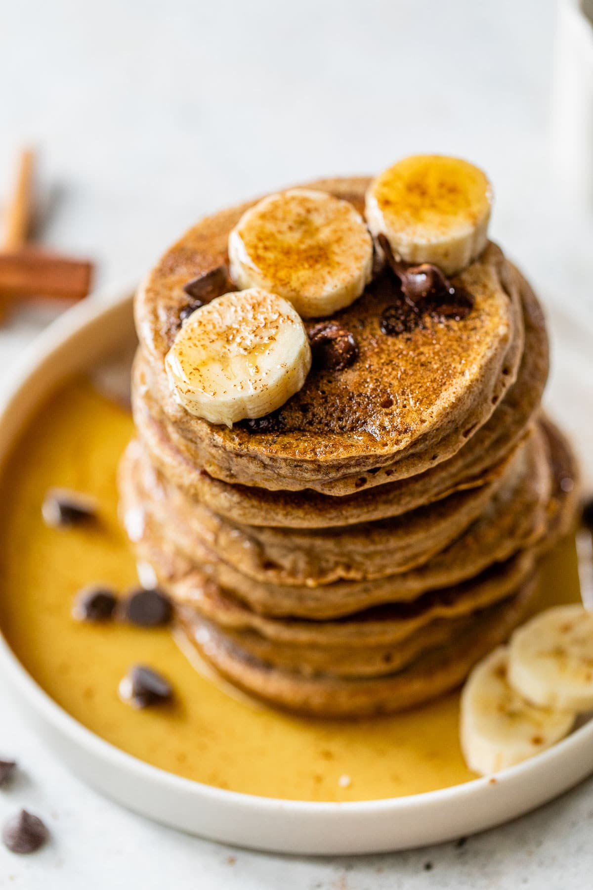 pancakes on a plate topped with chocolate chips, slices of banana and maple syrup