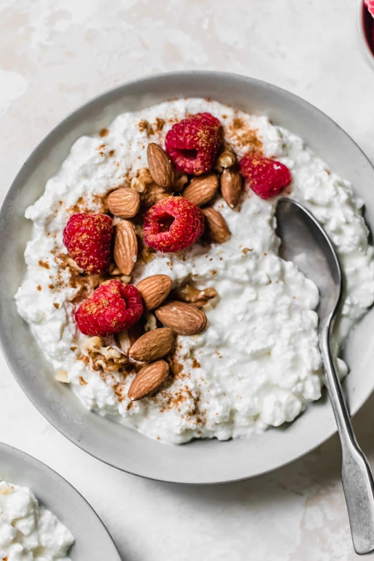 cottage cheese in a gray bowl topped with almonds and raspberries