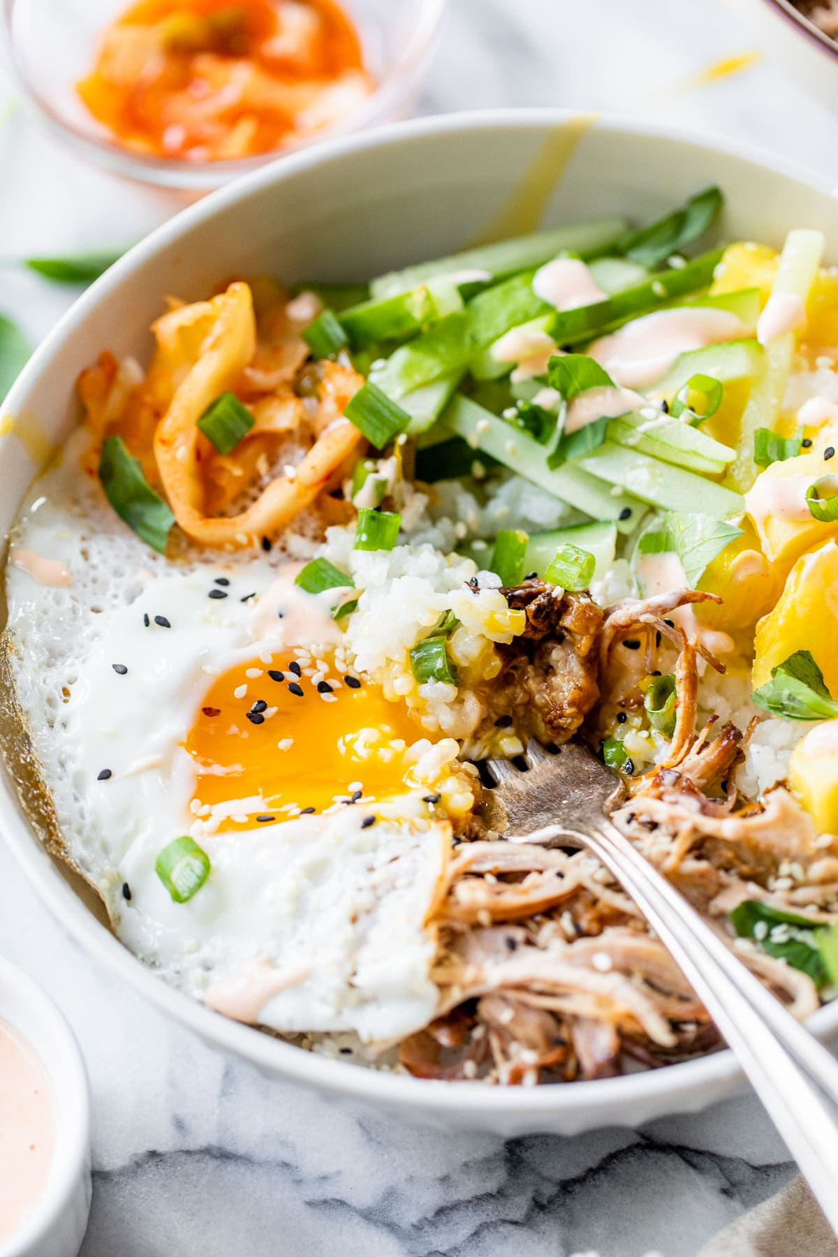 an over easy egg with runny yolk over pulled pork