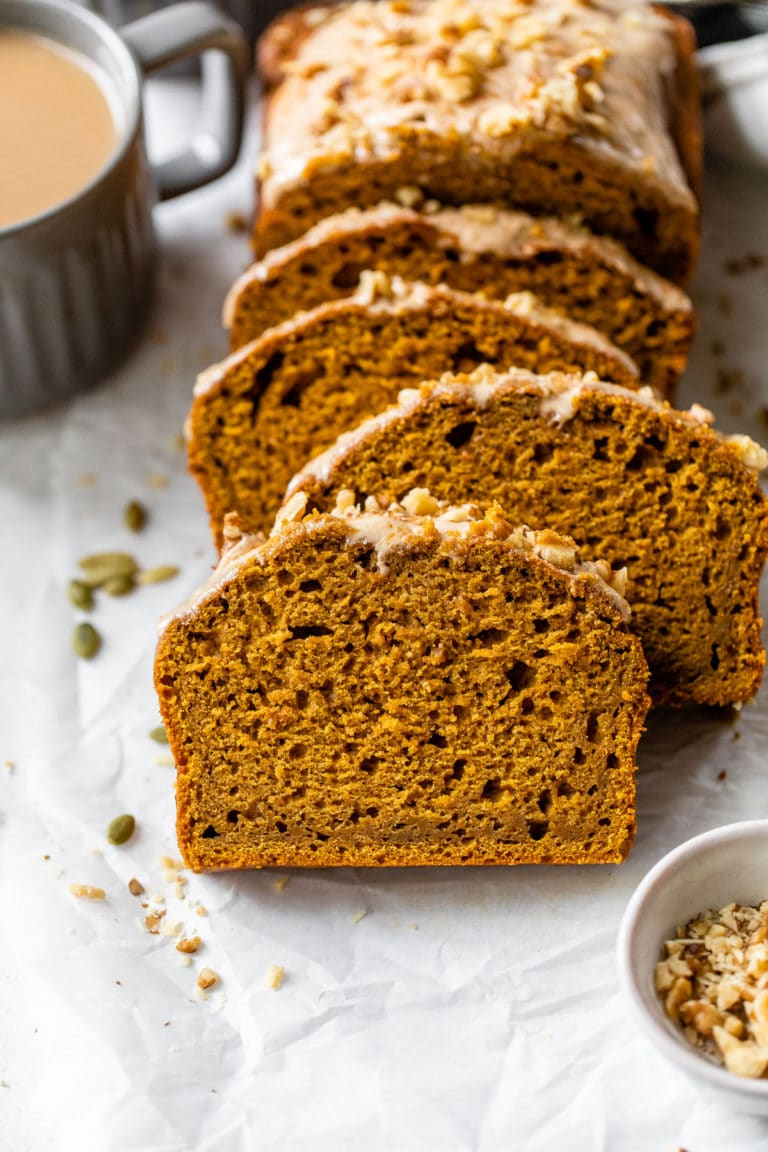 sliced pumpkin bread on parchment paper beside a mug of coffee