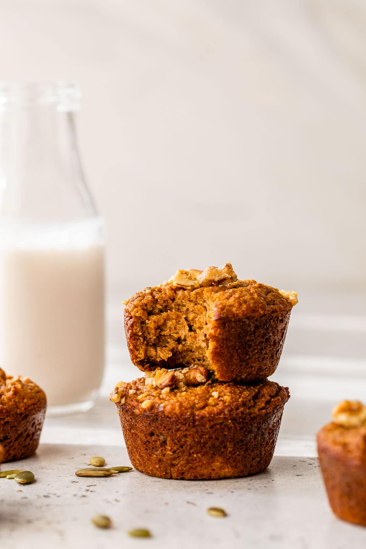two pumpkin muffins stacked on top of one another beside a tall glass of milk