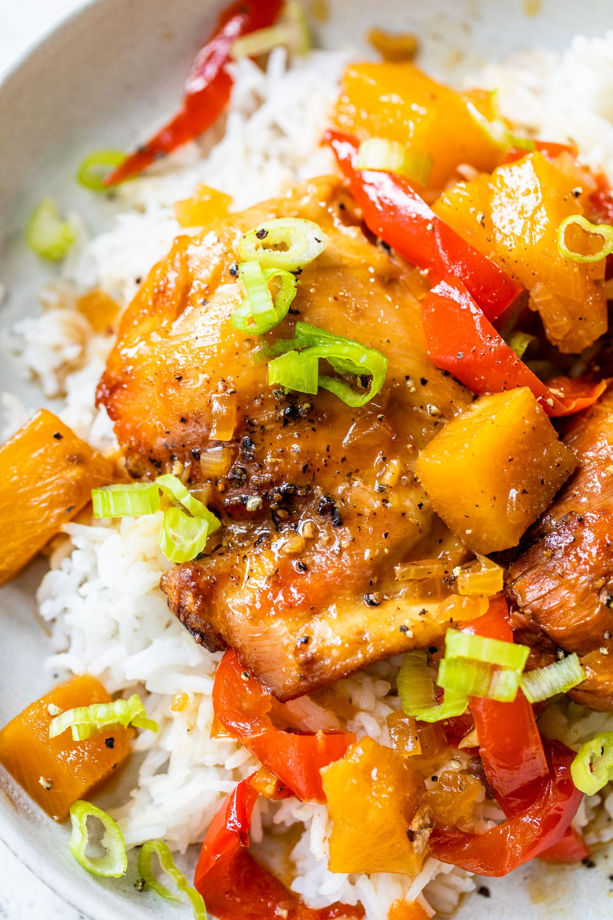 close up of a cooked chicken thigh with red bell peppers and diced pineapple