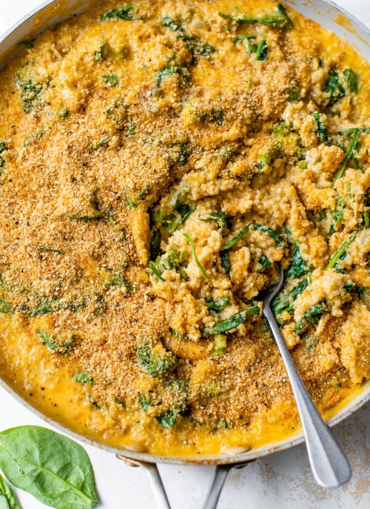 mac and cheese with quinoa and spinach in a skillet