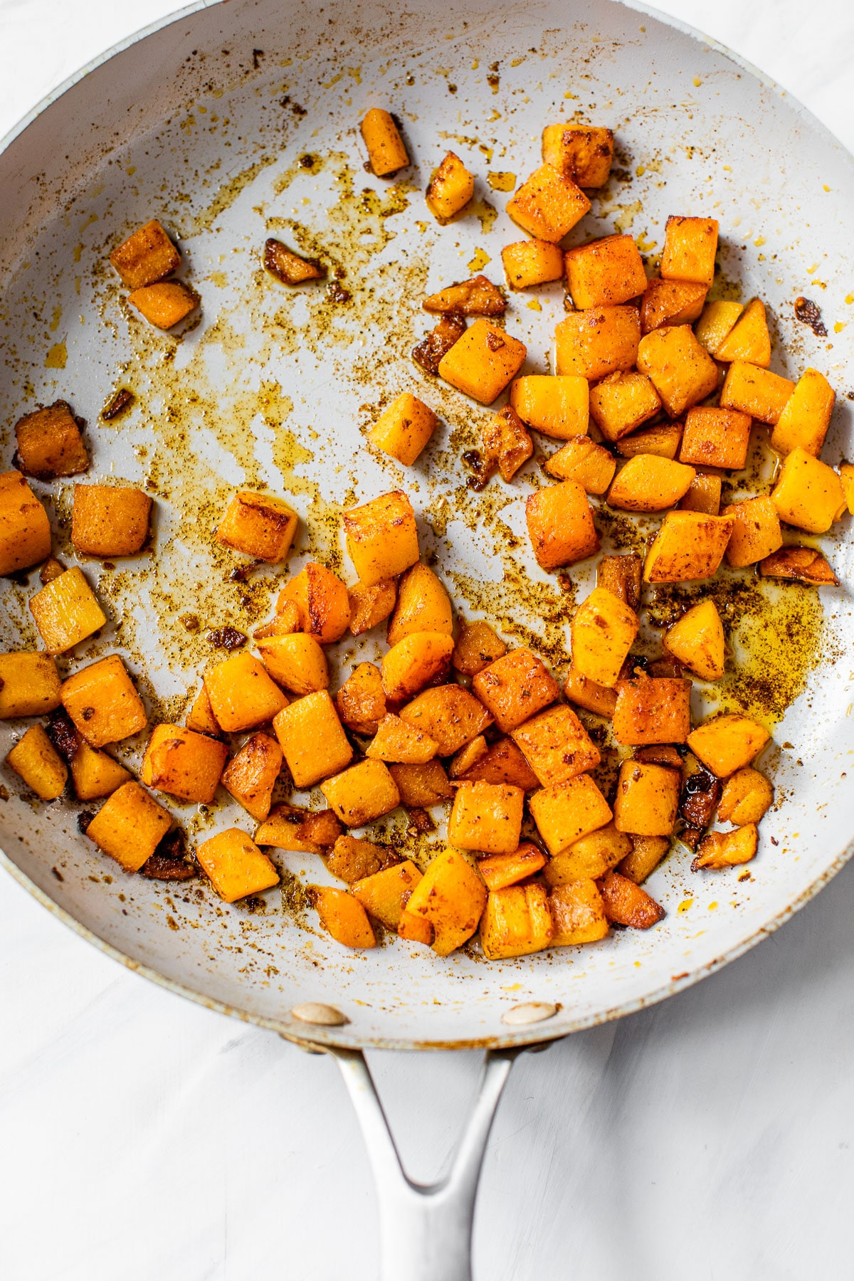 cooked diced butternut squash in a skillet
