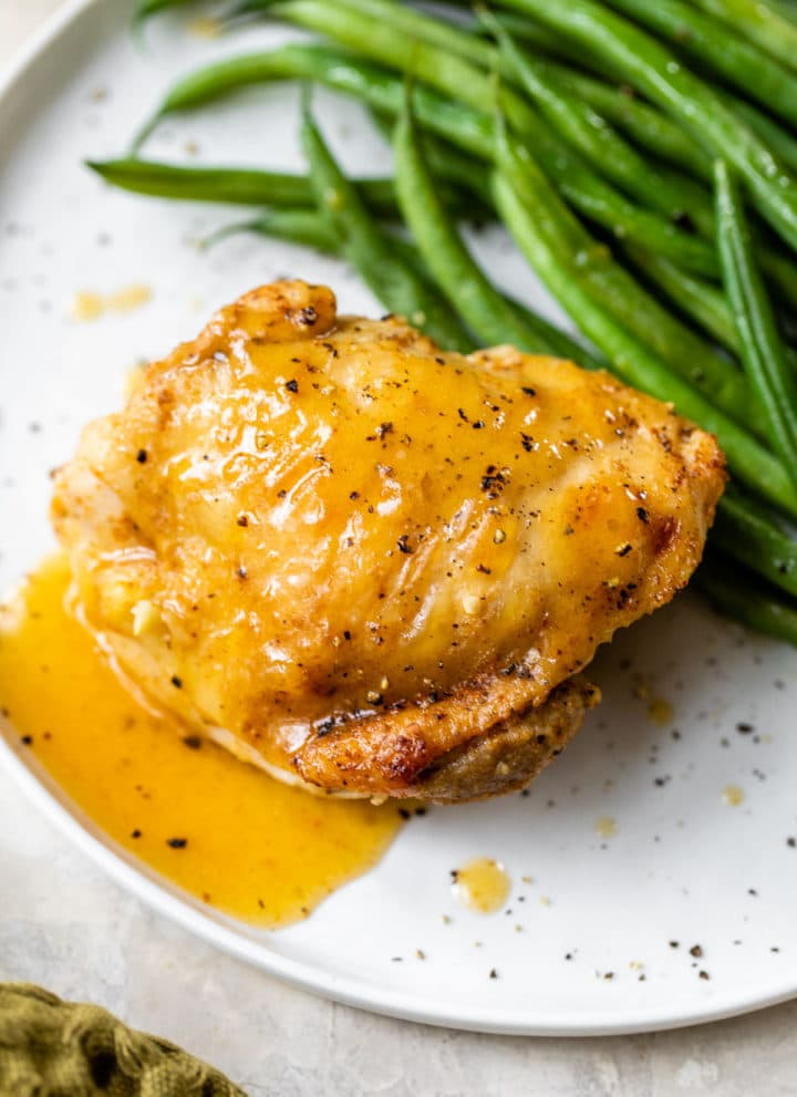 chicken thigh on a plate with gravy and green beans