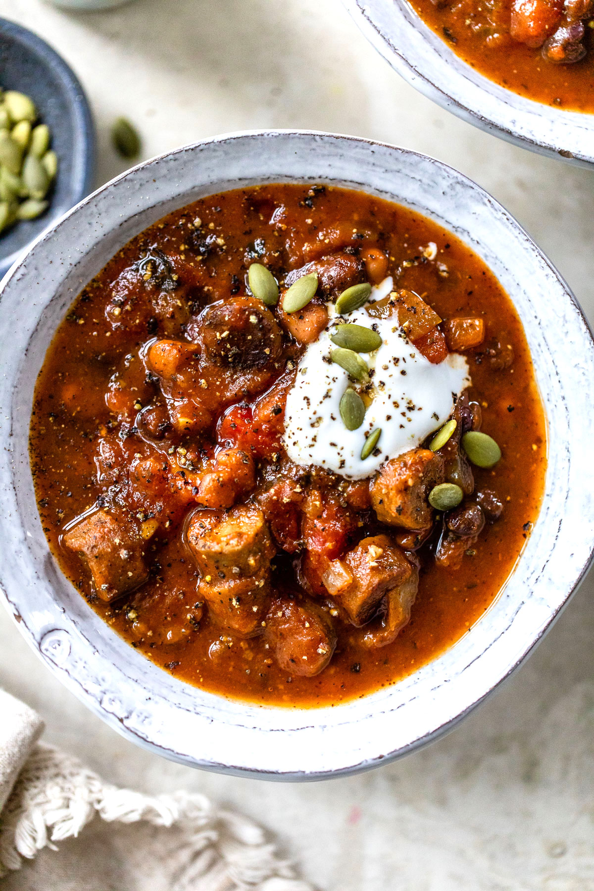 close up photo of a bowl of chili with beans and sausage