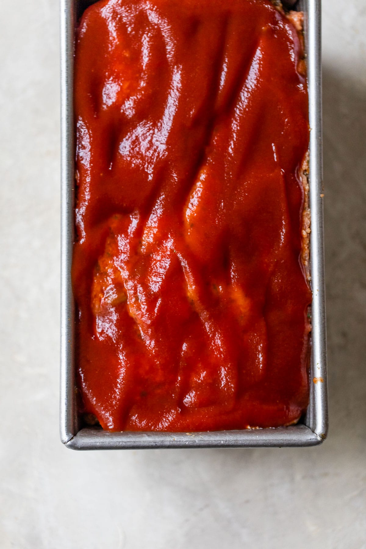 raw meatloaf with a ketchup glaze in a loaf pan