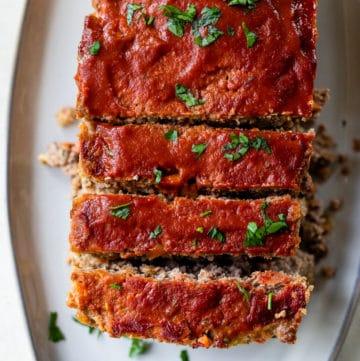 a sliced loaf of meatloaf on a serving platter